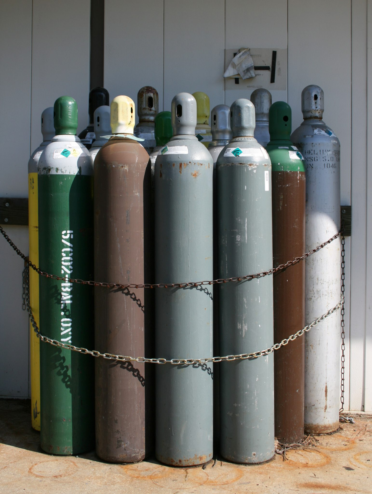 Compressed gas cylinders double chained to an exterior wall