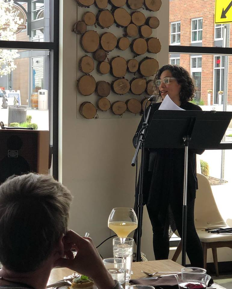 A photo of a woman standing with a metal stand reading poetry to a dining audience.