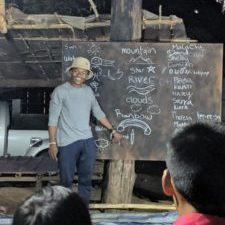 Malachi Chukwu teaches spelling to children in Palong Tribe