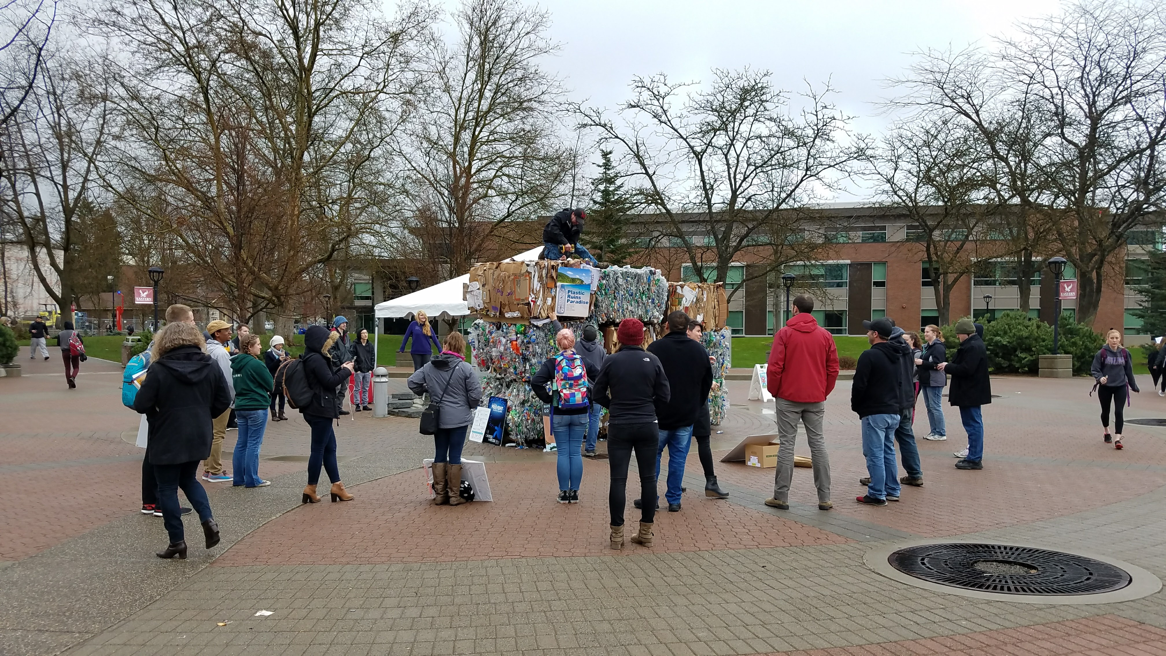 Students gather around nine trash bales are stacked in the campus mall with posters on each side promoting earth week.