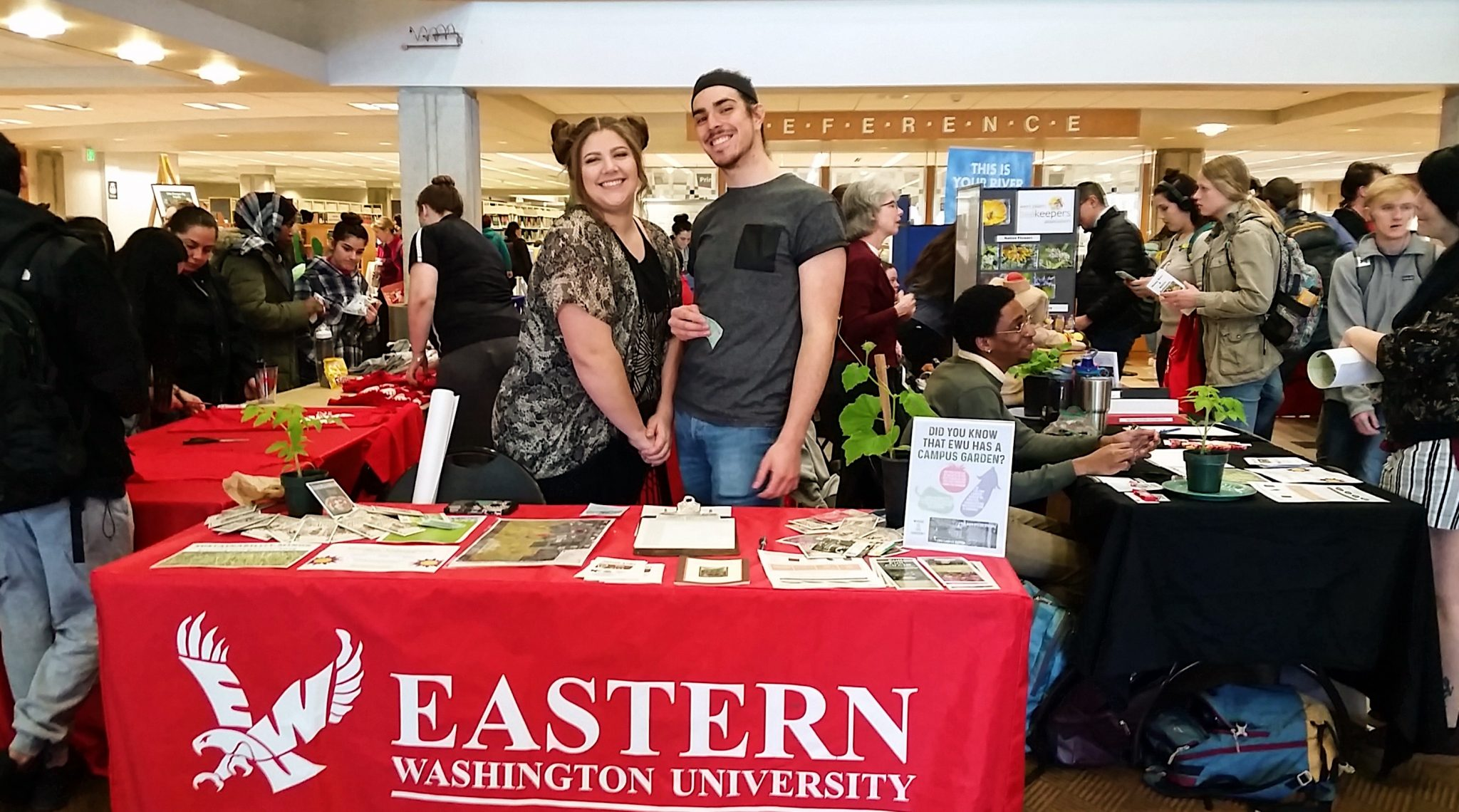 Two people pose behind their table for a picture in the crowded library.