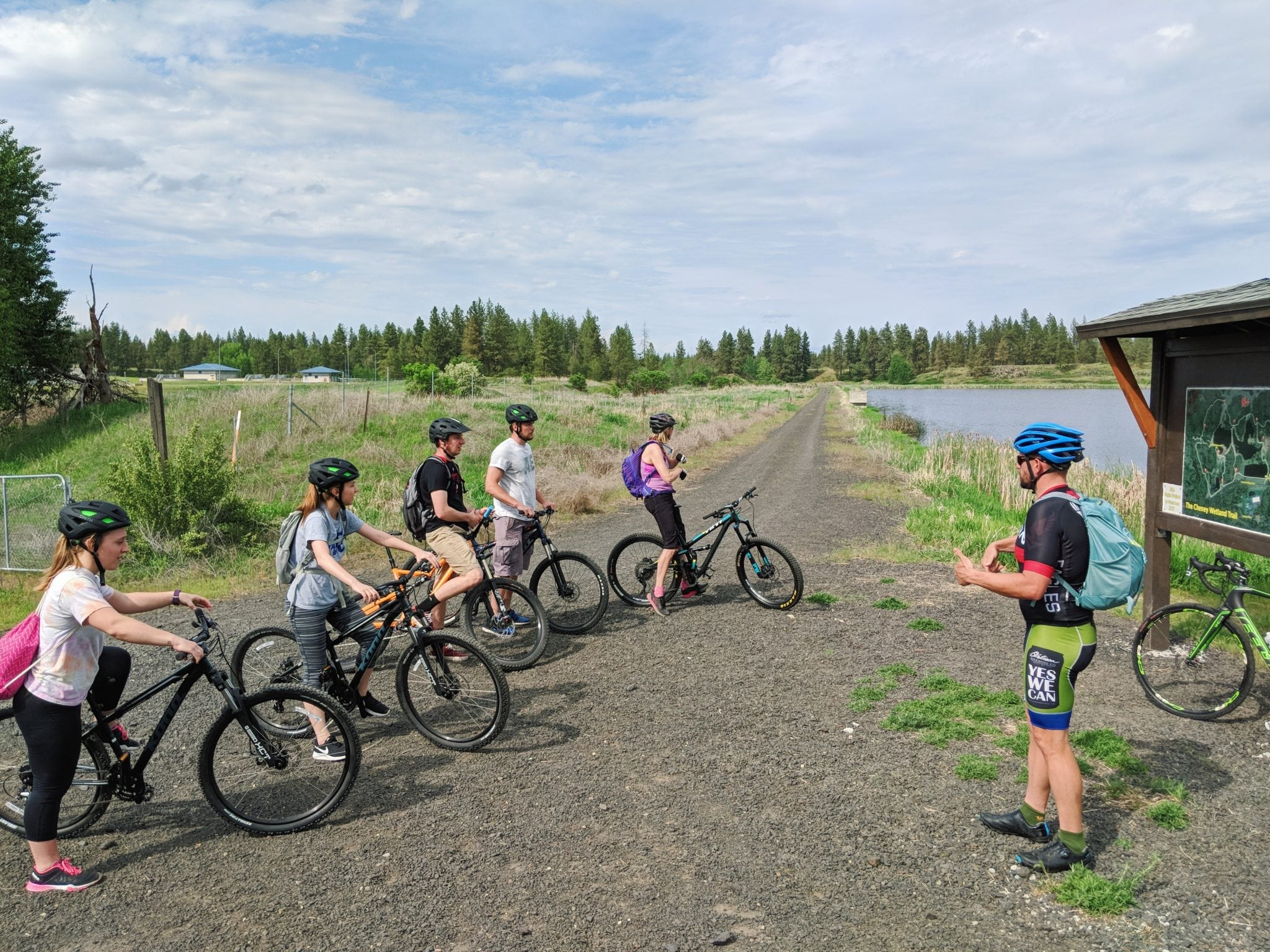 Five people standing over bikes by the Cheney wetlands listening to someone.