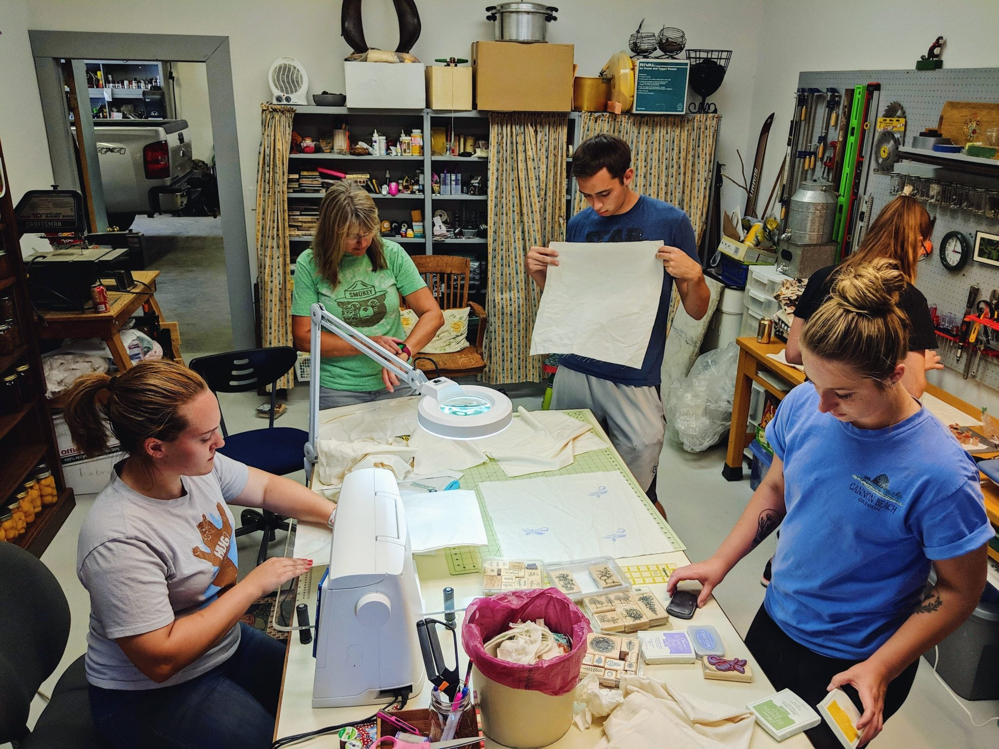 Five office workers are all busy working on their reuseable bags at Karen's house.