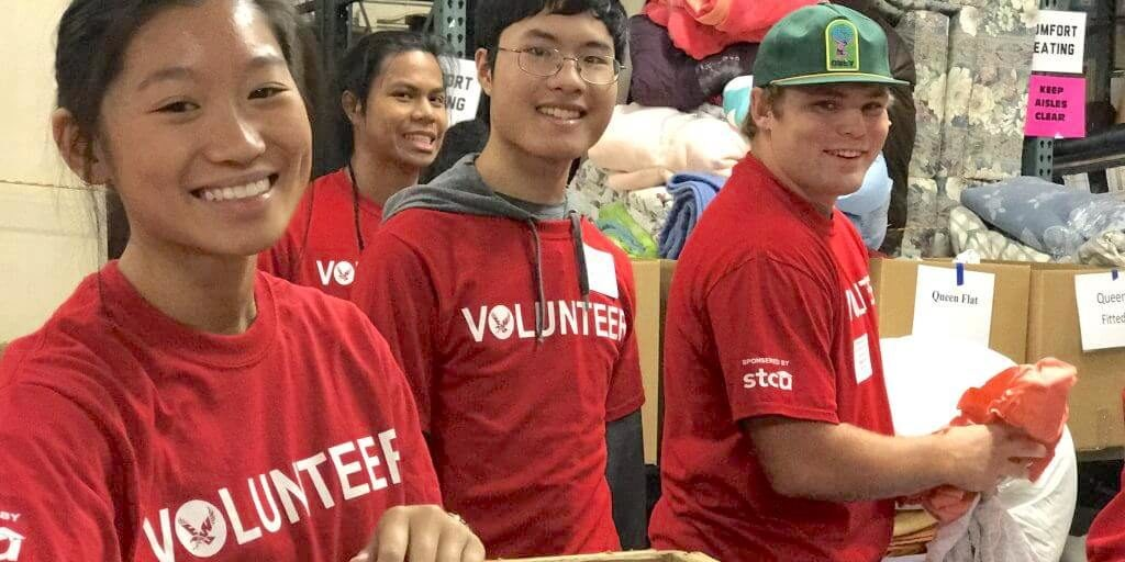 Students in red volunteer t-shirts smiling